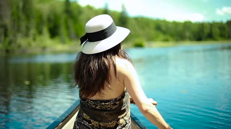 kano : Woman with fancy white hat canoeing on a lake, perfect weather day (package of 3 scenes including side views of the canoe) Stok Video