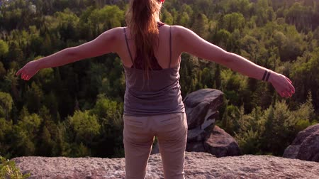 hate : Girl standing up and raising her hands while looking at the horizon on a mountain with rock cliffs at sunset - Traveling up from behind her