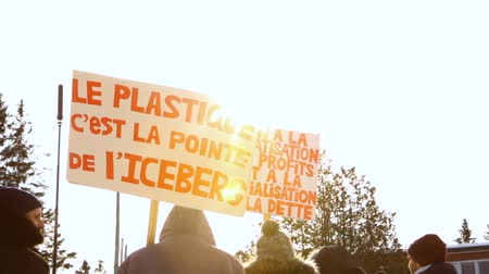 arrabaldes : Activists march during ecological rally. Low angle shot of protestors holding signs during an environmental rally. A French placard, saying the plastic is the tip of the iceberg, is seen as camera pans