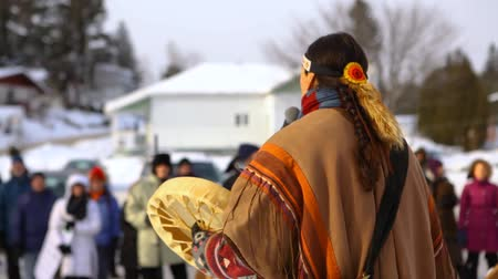 ралли : Environmentalists stage demonstration. A Native American plays music on a traditional drum, viewed from behind, during an outdoor gathering held by environmental campaigners.