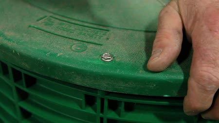 inventor : Man builds septic tanks in workshop. An extreme closeup view of a person operating a battery-powered drill to screw a plastic lid onto a sustainable septic tank. Techniques of a skilled tradesman.