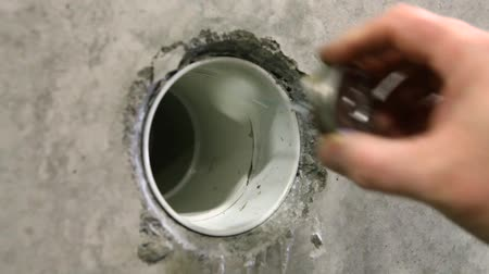 wynalazek : Man builds septic tanks in workshop. A short close-up clip of a plumber fixing a new waste disposal pipe into the base of an ecological septic tank. Glued and fixed joint through a concrete wall. Wideo
