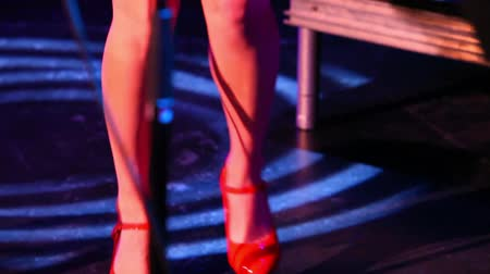 staging : Live band performing in a night club. Closeup footage of a female rockabilly singer entertaining people during a gig. Stylish artist wears red skirt and high heels whilst tapping feet along to music Stock Footage
