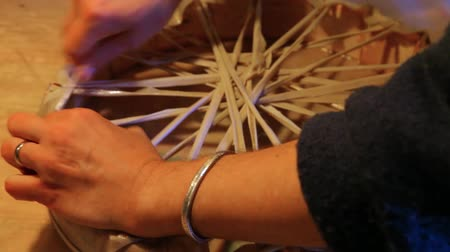 esneme : Hands of an artisan making sacred drum. Detailed view of a crafts person binding the stretched leather membrane of a shamanic drum. Knotting pattern on the back of a handcrafted native instrument.