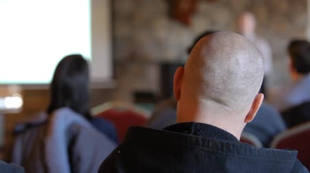 inventor : People at ecological product conference. A chubby guy with a shaved head is seen from behind during a lecture inside a conference hall. Man is seen blurred on stage with copy space on the left. Stock Footage
