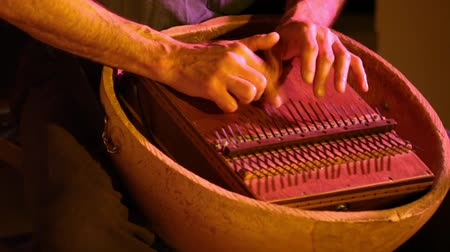 low lighting : Folk musicians perform intimate gig. Close up shots of an instrumentalist playing a mbira aka marimbula, a vintage finger piano originating from Africa. Played during an intimate concert.