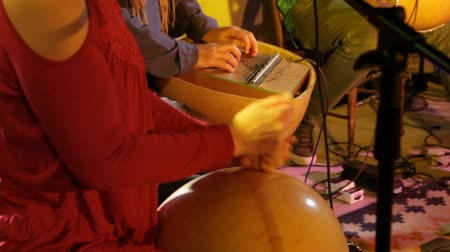 low lighting : Folk musicians perform intimate gig. A bohemian woman is viewed close up, using a calabash, a traditional African music instrument made from a large hollowed squash. Stock Footage
