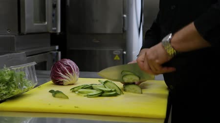 utěšený : Hands of a chef preparing fresh food. Close-up shots of a cook at work in an industrial kitchen, slicing a fresh green cucumber ready for evening service. Dostupné videozáznamy
