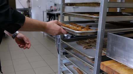 pastelaria : Hands of baker at work in kitchen. Close up footage of a Caucasian man checking shelves filled with freshly baked goods inside a bakery store.