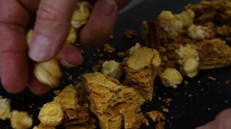 風味豊かな : Hands of a chef creating sweet treat. A close-up view of a chef making a luxurious dessert of honeycomb toffee and popcorn on a black slate plate inside a restaurant