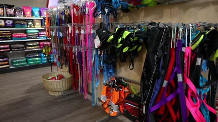 corredor : Products inside a pet superstore. Camera pans around the aisle inside a pet shop, showing display stands of dog leashes and bagged food in the background.