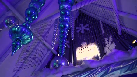 безделушка : Shimmering decoration during xmas party. Low angle footage of shiny Christmas decorations hanging from a vaulted ceiling. Stylish baubles and chandeliers hung from rafters indoors.