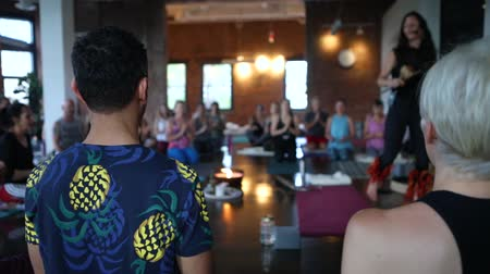 ajoelhado : Diverse group of people in yoga class. A large class of mixed people are seen kneeling on yoga mats indoors as an instructor teaches 101 salutations to the sun.