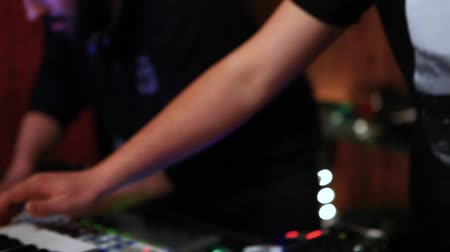 ajustando : Electronic musicians work in nightclub. Close-up and atmospheric shots of young Caucasian males performing a live electronic dance music set, using hands to control modern equipment. Stock Footage