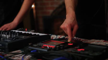 sztereó : Electronic musicians work in nightclub. Young men are shot closeup, controlling electric dance mixers whilst performing modern music to a young millennial crowd in a bar. Stock mozgókép