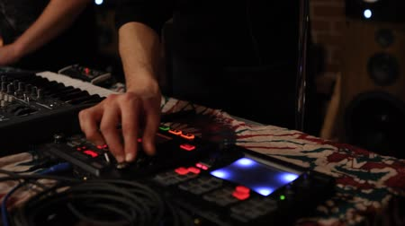 equalizador : Electronic musicians work in nightclub. Hands of young deejays are seen up-close, playing a live music set together inside a modern nightclub. Entertainment and nightlife.