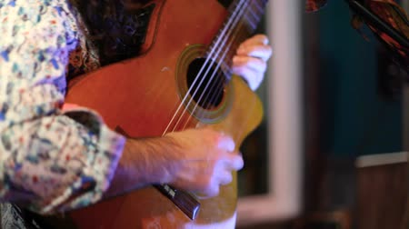 enstrüman : Guitarist plays to bar patrons by night. A jazz musician is viewed close up playing a vintage guitar on a small stage in a local bar Hands are seen plucking strings as he sways to music. Stok Video