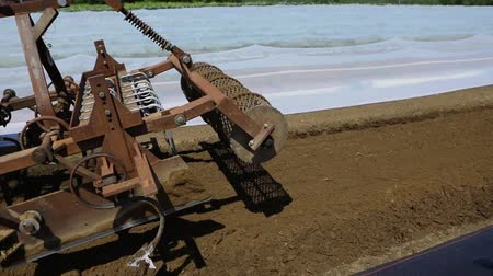 kertészet : Volunteer work on ecological farm crops. Closeup and slow motion footage of a farming plow attached to the front of a tractor as farmer prepares land for planting new crops, farm machinery at work.