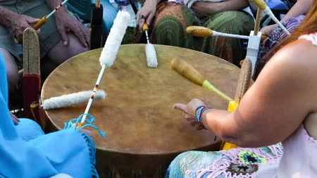 artifacts : Sacred drums at spiritual singing group. A close up view on a large mystical mother drum as a group of native musicians use traditional beater to perform cultural music outdoors.