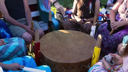 native american culture : Sacred drums at spiritual singing group. A closeup view as a shaman sprinkles sacred dirt on a mother drum as a group of people experience spirituality together in singing circle around native object.