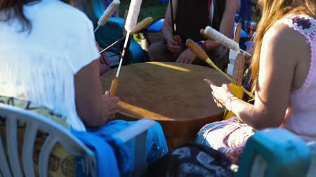 native american culture : Sacred drums at spiritual singing group. A group of friends celebrate native traditions in a local park, as they use traditional beater to play acoustic sounds on an ancient leather mother drum. Stock Footage