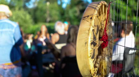 native american culture : Sacred drums at spiritual singing group. Closeup footage of a handmade indigenous leather drum hanging near a gathering of people as they sit in a singing circle during a mindful shaman ritual. Stock Footage