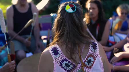 artifacts : Sacred drums at spiritual singing group. A woman in her 30s is seen from the back, wearing colorful traditional native style clothes and hair clip as people come together to experience powwow culture.