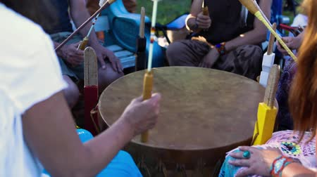 nativo americano : Sacred drums at spiritual singing group. A mixed group of individuals from all age groups are seen up-close in slow-mo, ecstatically beating a shamanic drum during a ceremonial ritual for mindfulness. Stock Footage