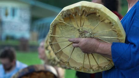 short clip : Sacred drums at spiritual singing group. A short clip shot close-up on the hand of an elderly woman, holding a handcrafted native drum during a powwow gathering, detail of the stretched & tied membrane Stock Footage