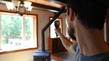 infra : Indoor damp & air quality (IAQ) testing. Slow motion footage of a domestic building surveyor using a handheld infra red thermal imaging camera during an indoor environmental quality (IEQ) assessment. Stock Footage