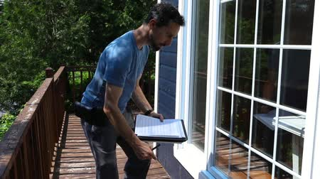 iaq : Indoor damp & air quality (IAQ) testing. Slow motion footage of a man using a notepad and clipboard as he walks around the exterior of a residential home, checking build quality and regulations. Stock Footage