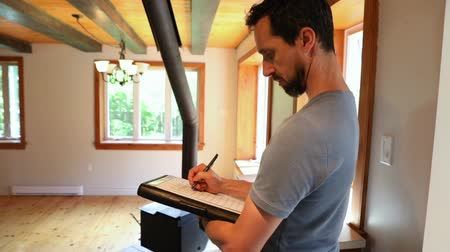 inspector : Indoor damp & air quality (IAQ) testing. A closeup short clip of a man checking items from a list and taking notes at work during the indoor environmental inspection of a domestic dwelling. Stock Footage