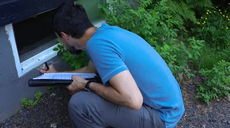 kural : Indoor damp & air quality (IAQ) testing. A short movie shot in slow motion of a professional residential property surveyor at work, inspecting exterior walls and taking notes on paper and a clipboard. Stok Video