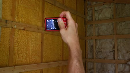 regras : Indoor damp & air quality (IAQ) testing. Point of view footage of an indoor environmental quality (IEQ) inspector at work, taking photographs with a small digital camera of exposed timber frame walls.