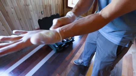 iaq : Indoor damp & air quality (IAQ) testing. A residential living quality assessor is seen close-up, preparing for work inside a domestic dwelling, stretching disposable gloves over large hands.