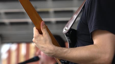 gitáros : Native band entertain at music festival. A short video shot in slow motion, giving a detailed view on the arm and hand of a guitarist playing a live set on stage during a cultural music concert.