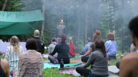 divinity : Diverse people enjoy spiritual gathering Calm and peaceful atmosphere is shot in slow motion during a sacred meditation class in nature, a spiritual guide is seen teaching mindfulness in background.