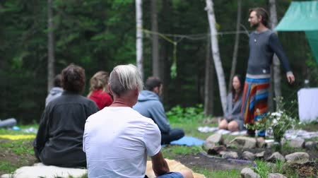chaman : Diverse people enjoy spiritual gathering Slow motion footage of a shaman guide teaching prayer and meditation techniques to an intergenerational group of people in a sacred forest clearing.