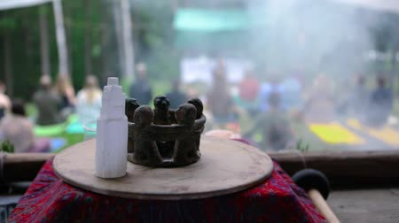 istenség : Diverse people enjoy spiritual gathering Sacred objects are viewed up close, as smoke is seen billowing in slow motion, setting the calm atmosphere during group meditation in a sacred forest clearing.