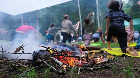 divinity : Diverse people enjoy spiritual gathering A slow-mo view of a mixed group of individuals experiencing sacred yoga behind a burning camp fire during a weekend of multicultural experiences. Stock Footage
