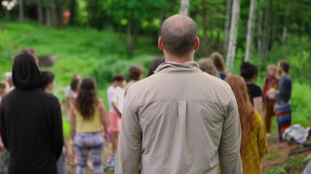 multigenerational : Diverse people enjoy spiritual gathering A middle aged caucasian guy with short balding hair is seen from the rear, standing amongst a large group of people enjoying spirituality in nature.