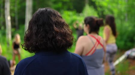 divinity : Diverse people enjoy spiritual gathering A woman with shoulder length black hair is seen from behind in slow motion, as a group of people experience expressive and free dance in a forest clearing. Stock Footage