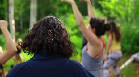 istenség : Diverse people enjoy spiritual gathering Slow motion footage of people moving from behind during an expressive and playful dance session in woodland during a multicultural festival in nature. Stock mozgókép
