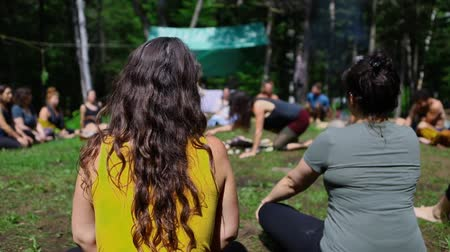 divinity : Diverse people enjoy spiritual gathering A close up and rear view on a lady with long dark hair and yellow vest top, as a mixed group of people are seen in slow motion sitting in a circle in a forest.