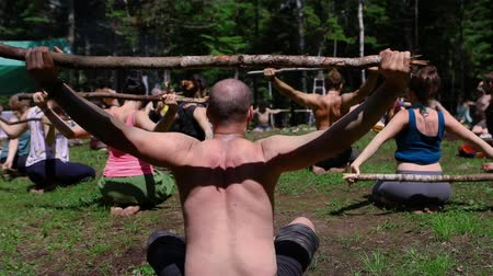 divinity : Diverse people enjoy spiritual gathering A close up and rear view on the back of a shirtless man in his forties, as people are seen in slow motion practicing mindful posture with a stick in nature. Stock Footage