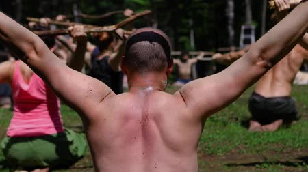 divinity : Diverse people enjoy spiritual gathering A middle aged caucasian guy is seen from behind in slow mo, experiencing mindful tai chi with a tree branch as people celebrate traditional cultures in nature.