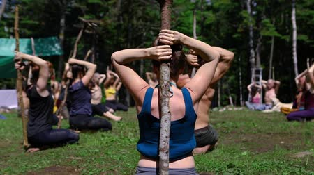 sanar : Diverse people enjoy spiritual gathering A mixed group of people are seen in slow motion, practicing mindful postures with sticks in a forest clearing during a native retreat in natural surroundings.
