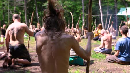 shaman : Diverse people enjoy spiritual gathering A slim shirtless caucasian man with shoulder length hair is shot from the rear, during a shamanic exercise using a large stick with a mixed group of individuals