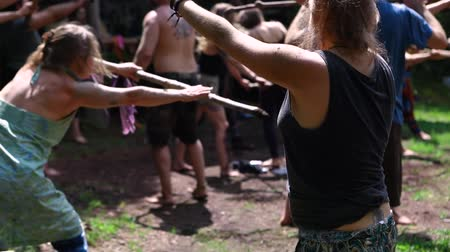 divinity : Diverse people enjoy spiritual gathering An intergenerational group of people are seen experiencing tai chi, lifting sticks during a multicultural festival in a sacred forest clearing. Stock Footage