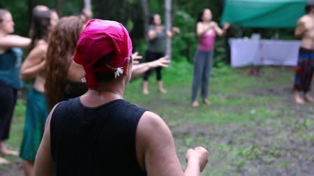 shaman : Diverse people enjoy spiritual gathering A caucasian woman wearing a colorful pink head scarf is seen in slow-mo, moving arms back and forth during sacred exercises to reach a relaxed state of mind.
